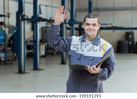 Professional car mechanic hello in auto repair service - stock photo