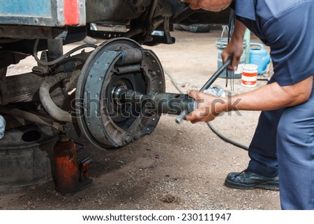 Professional car mechanic working in auto repair service. - stock photo