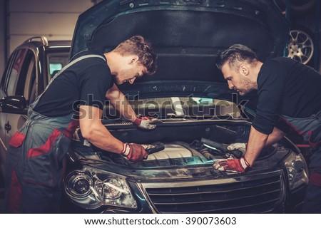 Professional car mechanics checking under hood in auto repair service. - stock photo