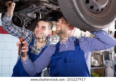 Professional car mechanics checking up pressure in tires at workshop  - stock photo