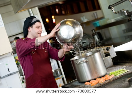 professional chef adding water into big pot for vegetable boiling in kitchen - stock photo