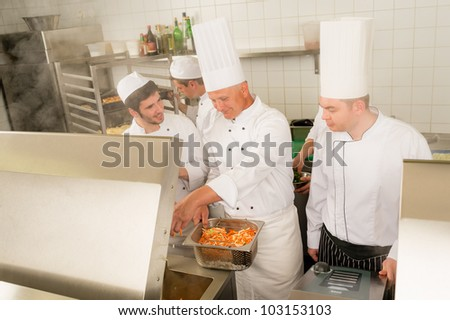 Professional chef cook with team prepare food in industrial kitchen - stock photo