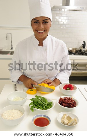 Professional chef cutting yellow pepper - stock photo
