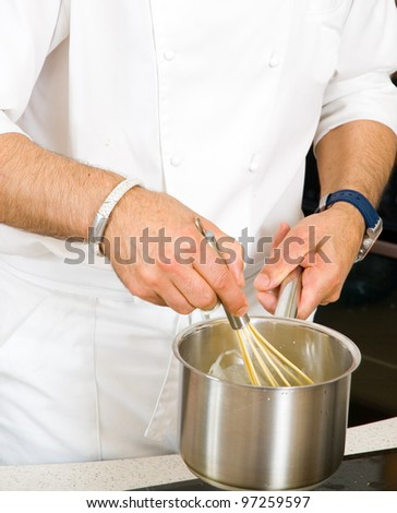 professional chef hands with kitchen utensils whisk and pan - stock photo