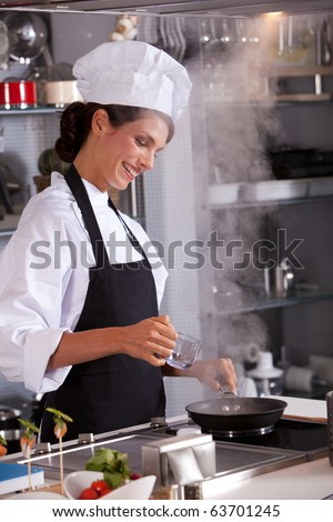 Professional chef in the kitchen adding some water to her dish - stock photo