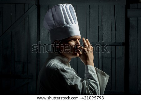 Professional chef in white hat with taste approval gesture - stock photo