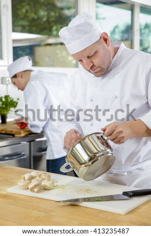 Professional chefs makes food dishes in large kitchen - stock photo