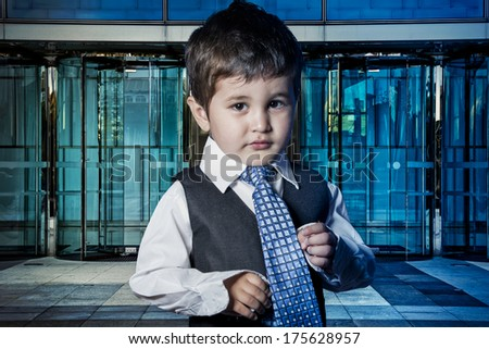 Professional, child dressed businessman with hands in his tie and skyscrapers in the background - stock photo