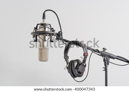 Professional condenser microphone with headphones on a stand. White background. - stock photo