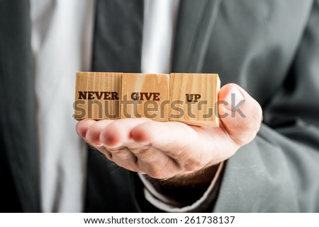 Professional consultant holding up three wooden cubes with a Never give up text. - stock photo