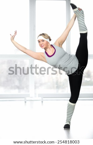 Professional dance lesson, sexy dancer female doing stretching exercises, standing in splits in class in white spots hall - stock photo