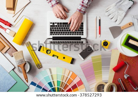 Professional decorator's hands working at his desk and typing on a laptop, color swatches, paint rollers and tools on work table, top view - stock photo