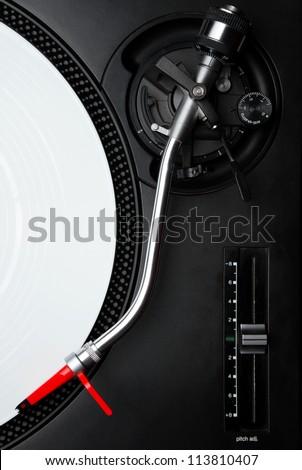 Professional DJ audio equipment - turntable needle on white vinyl record shot from above - stock photo