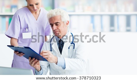 Professional doctor and his assistant working in the office, she is holding a clipboard and he is signing medical records - stock photo
