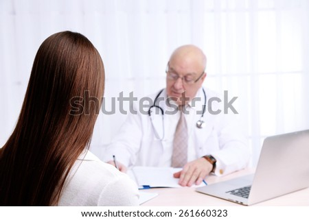 Professional doctor receiving patient in his office on white curtain background - stock photo