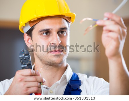 Professional electrician working with wires at client home - stock photo