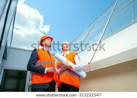 Professional engineer is explaining to his colleague his ideas about building. They are standing outdoors and smiling. The workers are looking aside with inspirations. The woman is carrying blueprint - stock photo