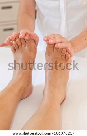 Professional feet massage - masseuse and female feet - stock photo