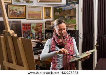 Professional  female artist getting ready to paint in a gallery holding a colorful artists palette and paintbrush in her hand - stock photo