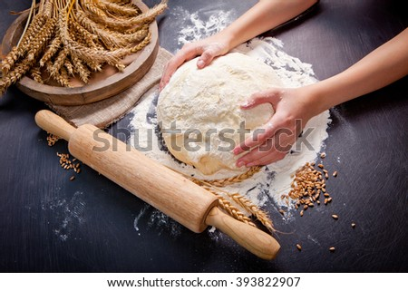Professional female baker cooking dough. Baking background with dough, flour and rolling pin. - stock photo