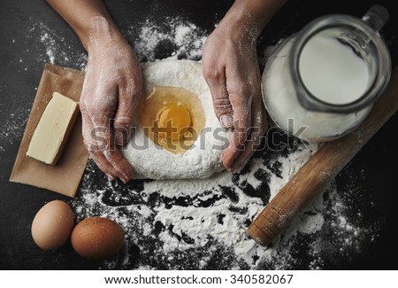 Professional female baker cooking dough with eggs, butter and milk for Christmas cookies.  - stock photo