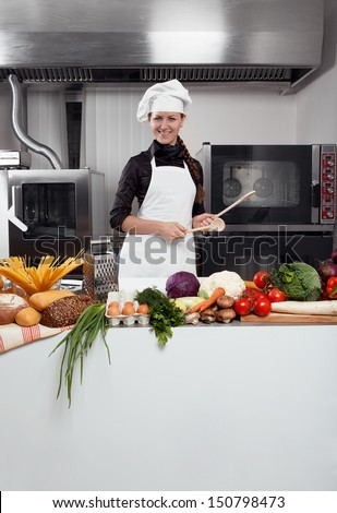 Professional female chef having fun and joy in a professional kitchen - stock photo