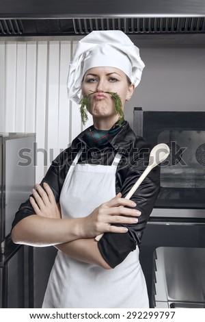 Professional female chef with a mustache of green dill on a professional kitchen - stock photo
