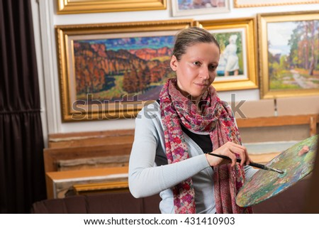 Professional female painting in a gallery holding a colorful artists palette and paintbrush in her hand - stock photo