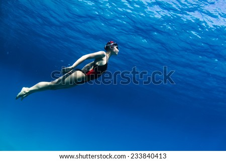 Professional female swimming underwater in blue sea with mirror on water surface and caustic effect on her skin  - stock photo