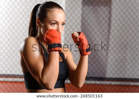 Professional fighter. Young beautiful woman in red boxing bandages ready to fight opponent in a boxing ring - stock photo
