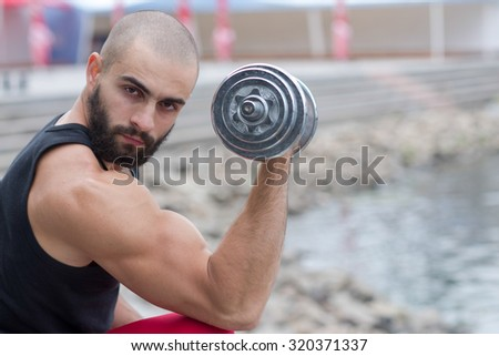 Professional fitness athlete trainer. Muscular male sportsman is training himself with dumbbells. Outdoors fitness sport concept. Street workout - stock photo