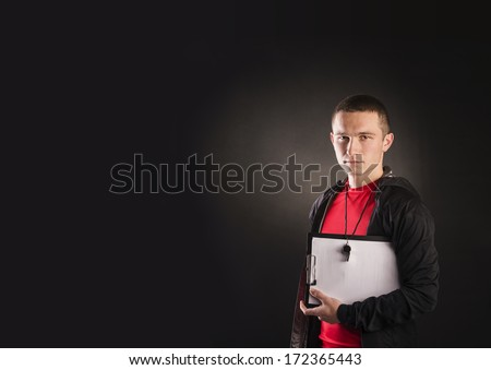 Professional fitness coach isolated on black background - stock photo
