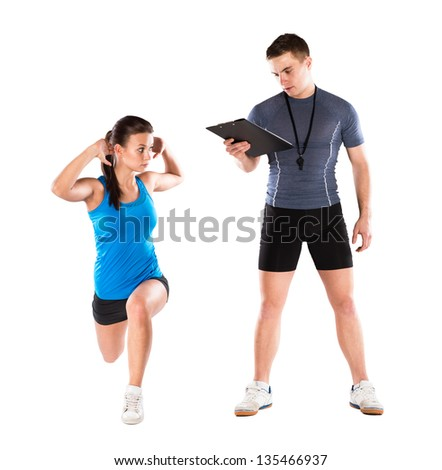 Professional fitness coach with beautiful young woman on white background - stock photo