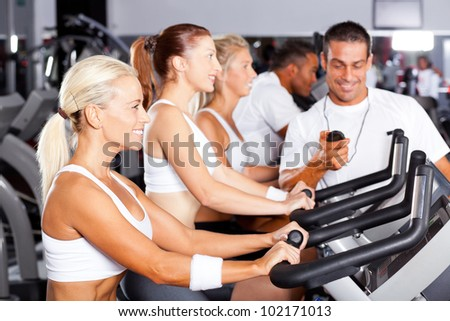 professional gym trainer monitoring trainees cycling performance - stock photo
