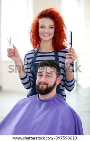 Professional hairdresser making new haircut  her handsome client - stock photo