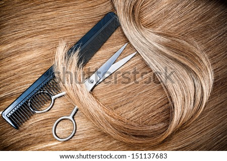 professional hairdresser scissors and comb on hair background - stock photo
