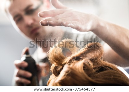 Professional hairdresser styling with hairspray long woman curly hair. Emotional detail of the hands making hot styling at hair salon. Color toned image. Blurred background. - stock photo