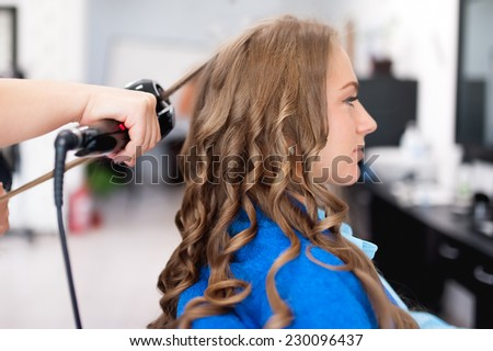 professional hairdresser using curling iron for hair curls at salon - stock photo