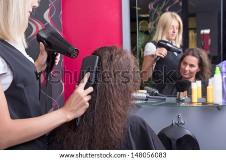 professional hairdresser with hairdryer and hairbrush drying female hair in beauty salon - stock photo