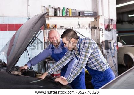 Professional happy adult mechanics repairing car of client - stock photo
