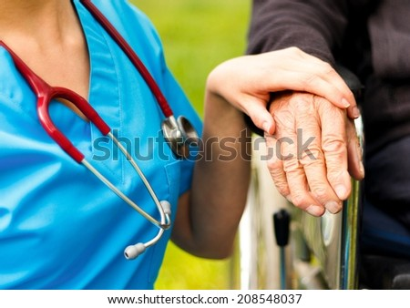 Professional help for elderly in wheelchair at the nursing homes. - stock photo