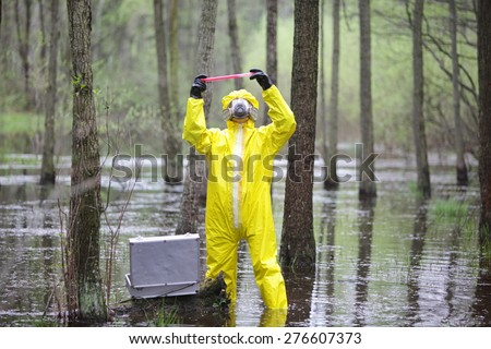 professional in protective coveralls with mini lab in contaminated environment - stock photo