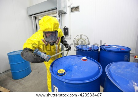Professional in uniform working with  barrels with chemicals - stock photo