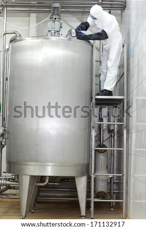 professional in white protective uniform,mask,goggles,gloves opening  large industrial process  tank in factory  - stock photo