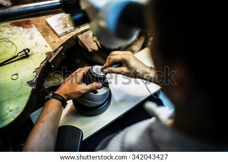 Professional jeweler working on a pieces of metal using an optical device - stock photo