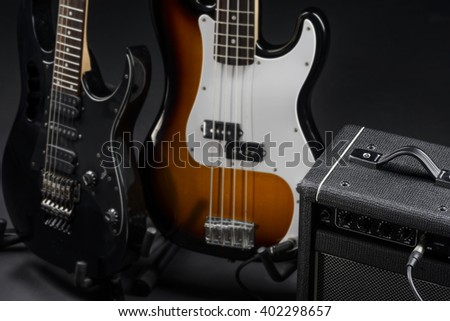 Professional level of playing musical intruments is needed to handle with this two beautiful guitars connected to an amp. Photo shoot in a studio. - stock photo