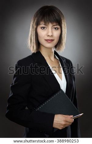 professional looking business woman holding a notebook and pen - stock photo