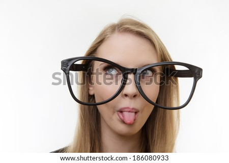 professional looking woman wearing large funny glasses sticking out her tongue - stock photo