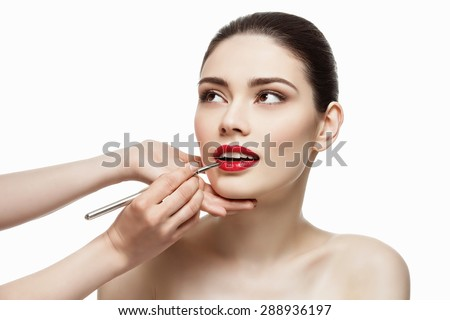 Professional make-up artist applying bright red lipstick on beautiful girl using special lip brush. Isolated over white background. - stock photo