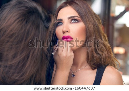 Professional Make-up artist applying makeup on a beautiful model - stock photo